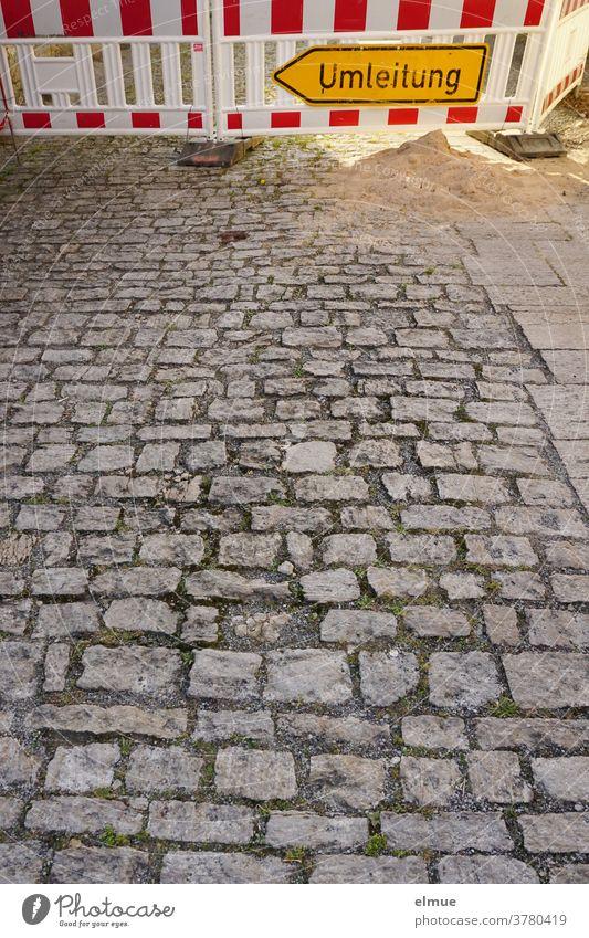 Ein gelbes Umleitungsschild und rot-weißes Absperrgitter vor einer Baustelle verhindern das Weiterfahren auf der grauen , gepflasterten Straße. Schild