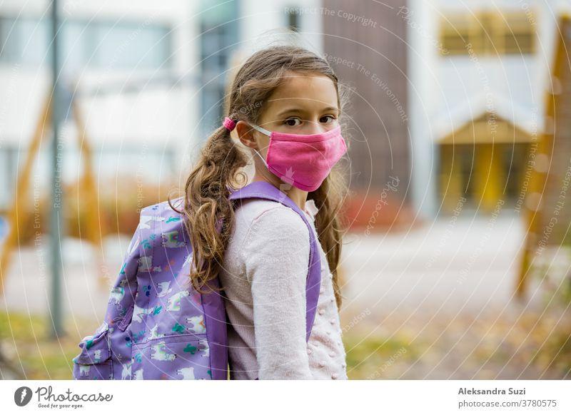 Schulmädchen mit wiederverwendbarer Schutzmaske aus Stoff beim Schulbesuch. Schulbildung während der Coronavirus-Pandemie. Sicherheitsmaßnahmen und soziale Distanzierung