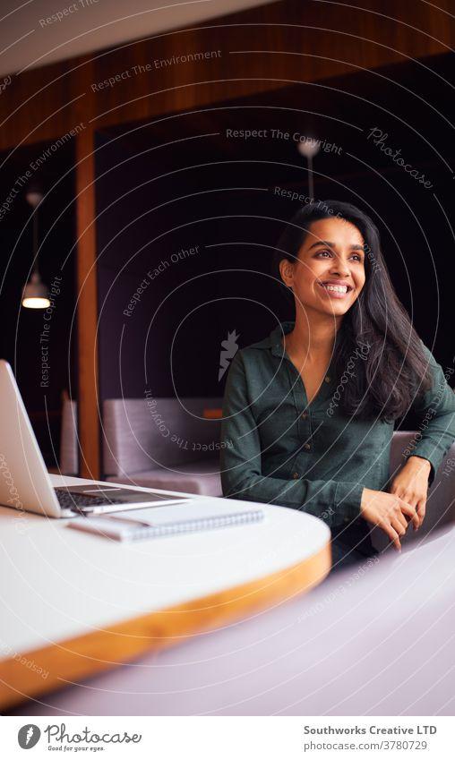Geschäftsfrau sitzt am Besprechungstisch und arbeitet am Laptop in einem modernen Großraumbüro Business Geschäftsfrauen Sitzung Büro Sitzen Sitzungssaal Tisch