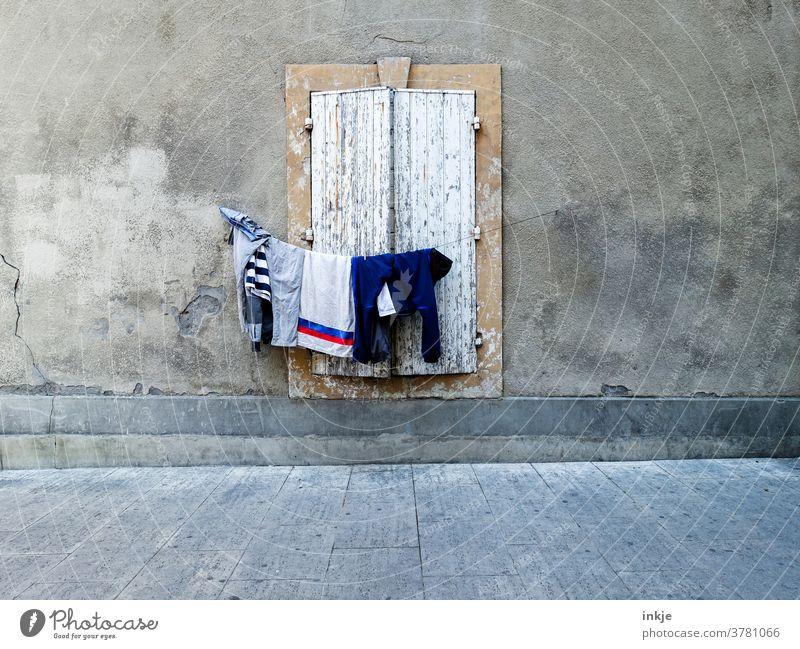 behängte Wäscheleine vor geschlossenem Fenster Fassade menschenleer farbfoto draußen Haus Wand trist arm Fensterladen geschlossen zu braun beige grau trocknen