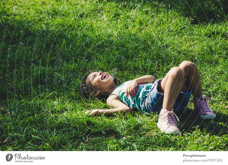 Kleines Mädchen ruht im Gras und lächelt an einem sonnigen Tag Kind Lügen Natur grün Lächeln Frühling Kinder sich[Akk] entspannen Feld Sonne Wiese Person Blume