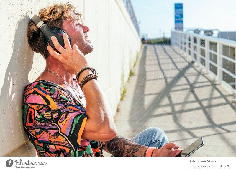 Entspannter männlicher Skater beim Musikhören in der Stadt zuhören Mann sich[Akk] entspannen genießen urban trendy Hipster Kopfhörer Skateboard Straße verträumt
