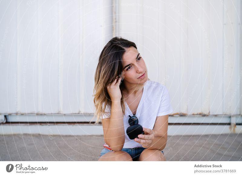 Junge Frau setzt Kopfhörer auf der Straße auf Ohrstöpsel angezogen ausrichten Drahtlos tws echte drahtlose Apparatur Gerät zuhören Aktivität jung modern