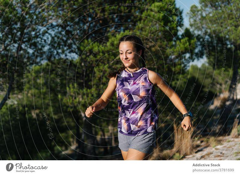 Aktive Frau läuft auf Pfad im Wald Nachlauf laufen Berge u. Gebirge aktiv Training Sport Athlet positiv jung Natur Fitness Lifestyle Sportkleidung