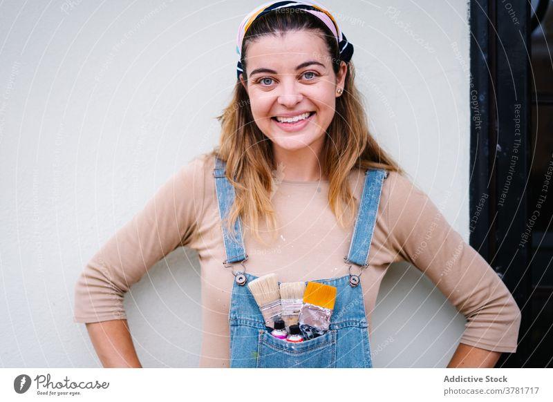 Positive Handwerkerin mit Pinseln schaut in die Kamera Frau Künstler Kunstgewerbler Farbe Pinselblume kreativ Glück Lächeln Porträt Beruf Talent Arbeit heiter