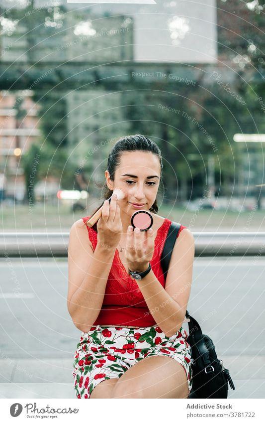 Junge Frau mit Spiegel Anwendung erröten auf der Straße Make-up bewerben Schönheit Kosmetik urban modern jung brünett Glamour Stil Mode Lifestyle Zeitgenosse