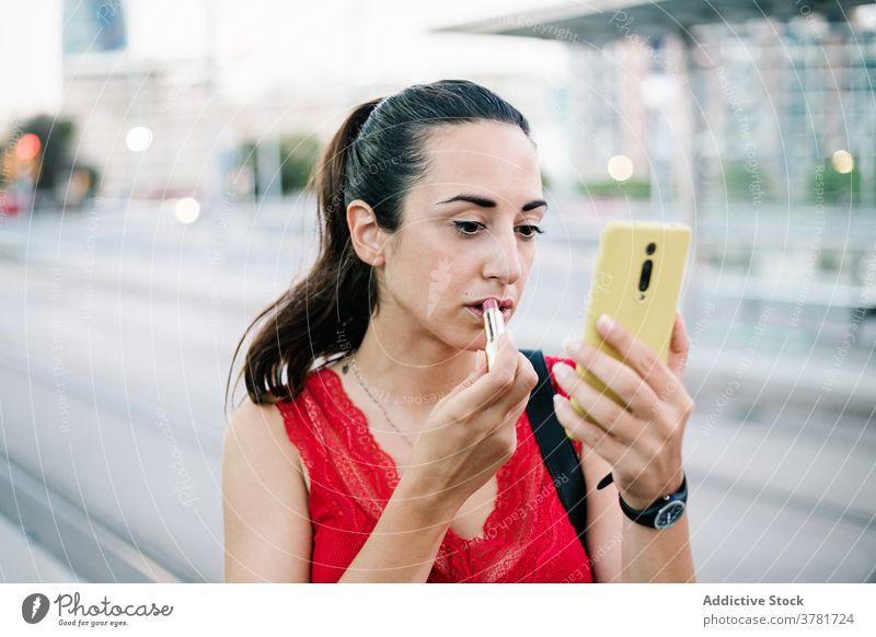 Junge Frau mit Smartphone trägt Lippenstift auf der Straße auf Make-up bewerben Schönheit Kosmetik Mobile urban modern Funktelefon Telefon Gerät Apparatur jung