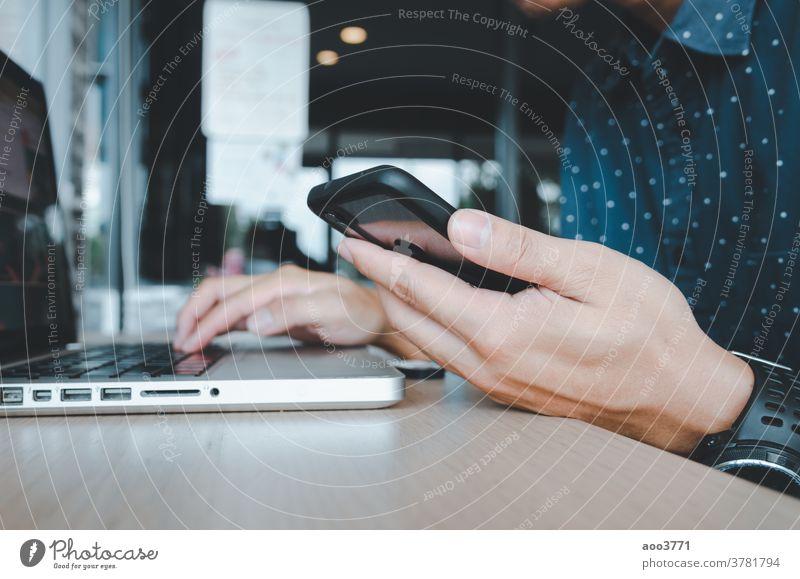 Mann hält ein Mobiltelefon und einen Laptop an einem Schreibtisch Telefon Mobile Tisch Technik & Technologie Zelle Internet Smartphone Business Computer klug