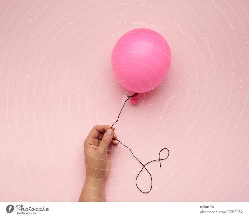 weibliche Hand, die einen aufgeblasenen rosa Luftballon auf rosa Hintergrund hält Air Arme Ball Ballon blanko Nahaufnahme Frau gefüllt Schwimmer Helium Halt