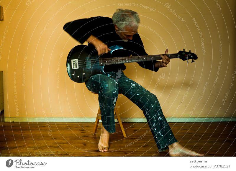 Jemand spielt Bass Bassist Hocker Instrument Mann human Musik musizieren Sonde sitz sitzen sitzplatz spielen üben übung übungsraum musikschule Zimmer Wohnung