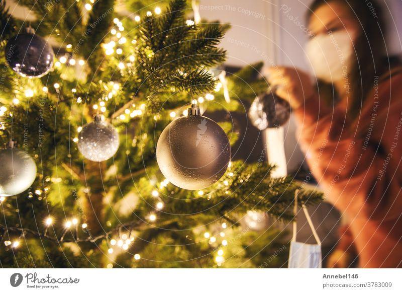 Junge Frau schmückt einen Weihnachtsbaum mit medizinischer Sicherheitsmaske für Covid-19, Coronavirus und Weihnachtskonzept, schöner Feiertag Neujahr heimwärts