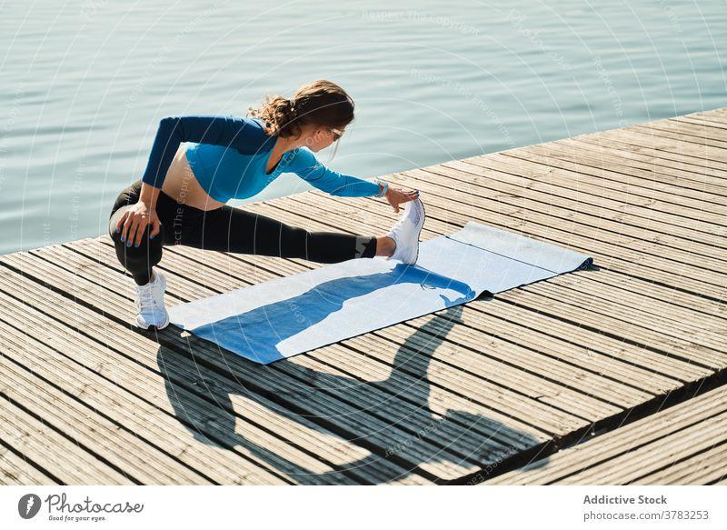 Schlanke Frau in Sportkleidung beim Training am Pier Dehnung Bein passen schlank Fitness Übung Stauanlage sportlich aktiv Aufwärmen Gesundheit beweglich
