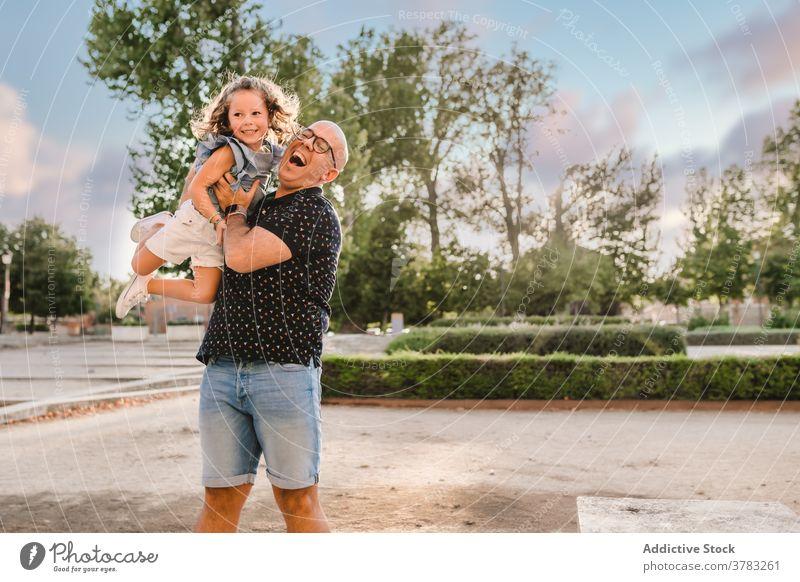 Positive Mann spielt mit niedlichen Mädchen auf der Straße Vater Tochter werfen Spaß haben spielen Spiel Vaterschaft Liebe Großstadt Zusammensein Wochenende
