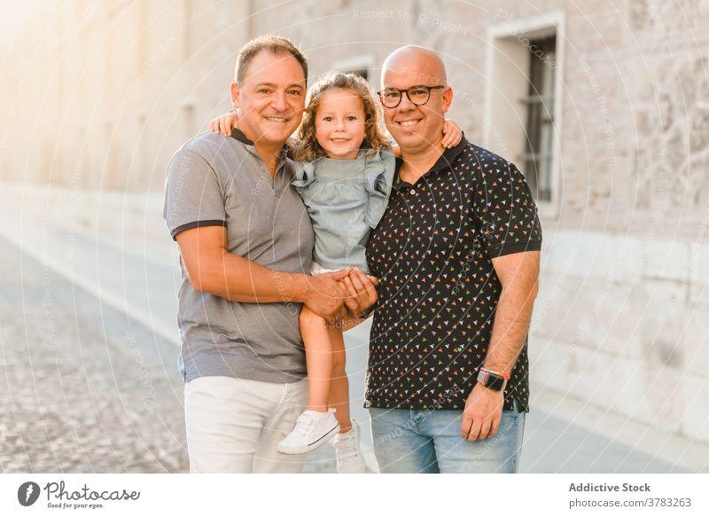 Erfreute LGBT-Familie auf der Straße lgbt Zusammensein Vater Männer schwul Paar Kind unterhalten Großstadt Durchgang Wochenende Sommer Spaziergang Glück Freude