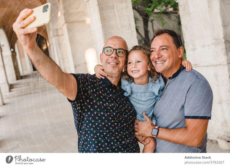 Fröhliche LGBT-Familie nimmt Selfie in der Stadt lgbt Kind Paar schwul Männer Mädchen Smartphone Homosexualität Zusammensein fotografieren Selbstportrait