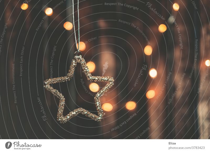 Weihnachtsdekoration. Stern als Christbaumschmuck und Lichterkette im Hintergrund. Weihnachten Anhänger Weihnachten & Advent Dekoration & Verzierung