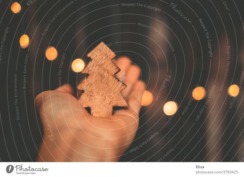 Weihnachten. Hand hält einen Weihnachtsbaum aus Holz. Dekoration Weihnachtsdekoration Weihnachten & Advent Baum Tannenbaum