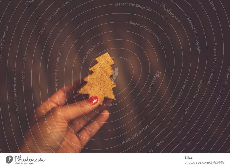 Hand hält einen Tannenbaum aus Holz vor braunem Hintergrund. Weihnachten. Dekoration natürlich geschnitzt halten hintergrund warm Weihnachtsdekoration