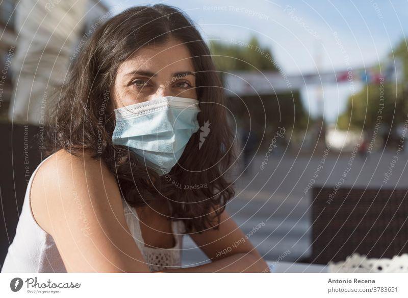 Hübsche Frau in Bar-Terrasse mit Gesichtsmaske, die in die Kamera schaut Mundschutz covid-19 Coronavirus Verschmutzung Allergie chirurgisch Person Menschen