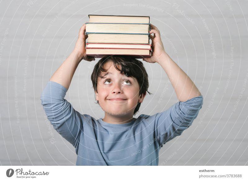 glückliches Kind mit Büchern auf dem Kopf Buch Bildung Weisheit zurück zur Schule Kindheit Intelligenz Wissen lernen Schüler Denken genial Schuljunge Lächeln