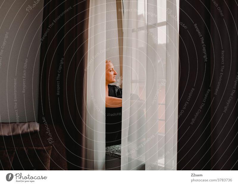 Junge Frau sitzt auf dem Fensterbrett und Blickt nach draußen Junge frau blickt fenster fensterbrett nachdenken fernblick vorhänge schön attraktiv wärme