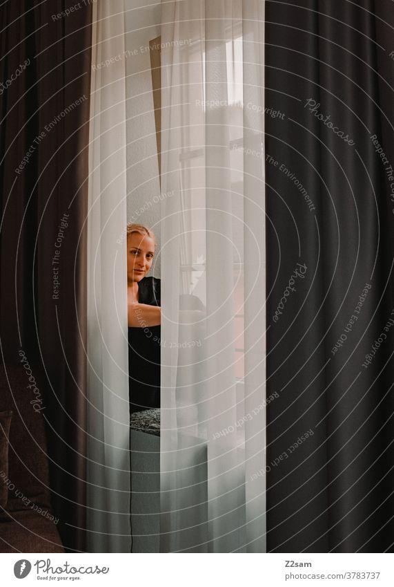Junge Frau sitzt auf dem Fensterbrett Junge frau blickt fenster fensterbrett nachdenken fernblick vorhänge schön attraktiv wärme glücklich blond Porträt