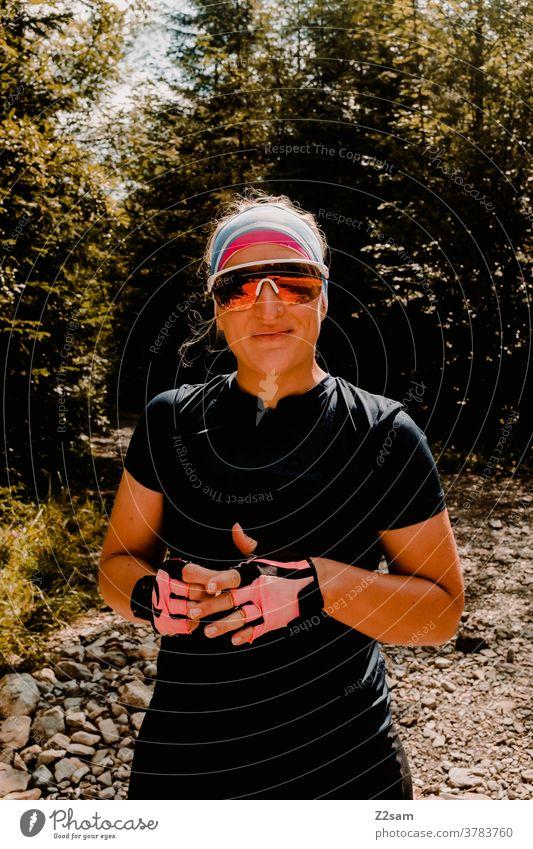 Junge Frau mit Radoutfit radfahren sport sportlich trikot radhandschuhe sonnebrille style modern hübsch schön blond junge frau lachen lächeln glücklich fröhlich