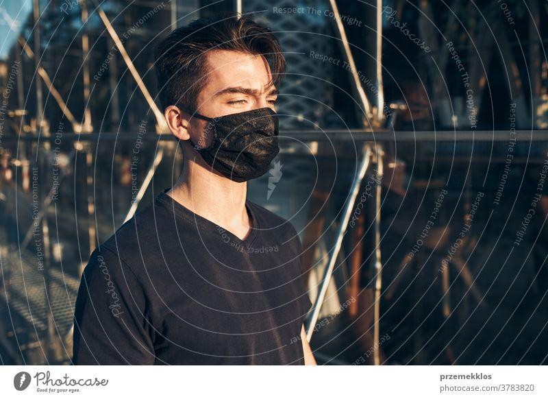 Junger Mann geht im Stadtzentrum entlang der Glasfront eines Geschäfts und trägt die Gesichtsmaske, um eine Virusinfektion zu vermeiden Pflege Kaukasier Zentrum