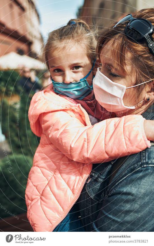 Familienmutter und ihre Tochter stehen auf einer Straße in der Innenstadt und tragen die Gesichtsmasken, um eine Virusinfektion zu vermeiden Anruf Pflege