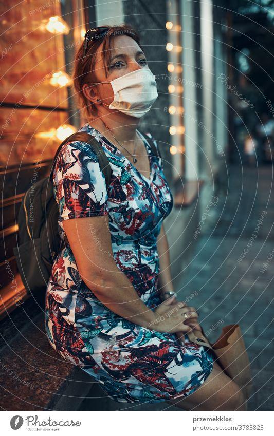 Junge Frau, die nach einem Einkauf im Stadtzentrum im Freien an der Café-Front sitzt und die Gesichtsmaske trägt, um eine Virusinfektion zu vermeiden Kaukasier