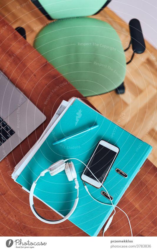 Handy-Kopfhörer von Binder auf dem Schreibtisch im Home-Office Ordner Textfreiraum täglich Schriftstück heimwärts im Innenbereich Internet Job lernen Lernen