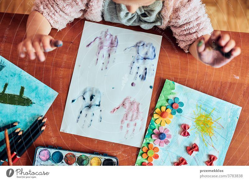 Kleines Mädchen im Vorschulalter, das mit bunten Farben und Buntstiften ein Bild malt Kind Malerei Farbstoff Bildung farbenfroh Kunst heimwärts Papier Kindheit