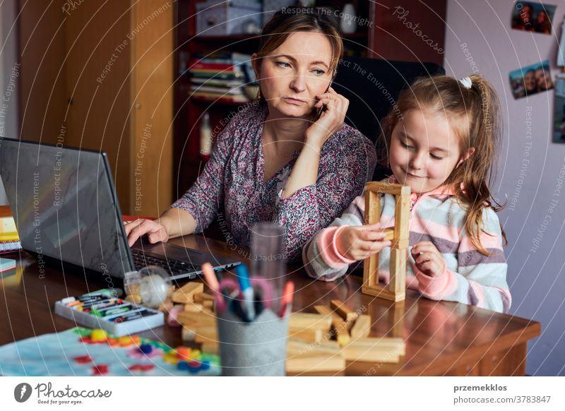 Mutter arbeitet bei der Erledigung ihrer Arbeit aus der Ferne während eines Video-Chat-Call-Stream-Online-Kurses Webinar auf einem Laptop von zu Hause aus, während ihre Tochter mit einem Ziegelsteinspielzeug spielt