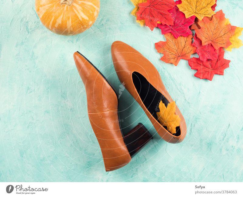 Weibliche Schuhe in trendiger Herbstfarbe mit Blättern fallen Mode Oktober Spaziergang Frau Hintergrund trendy Farbe Pumpe Leder Kürbis saisonbedingt Symbole