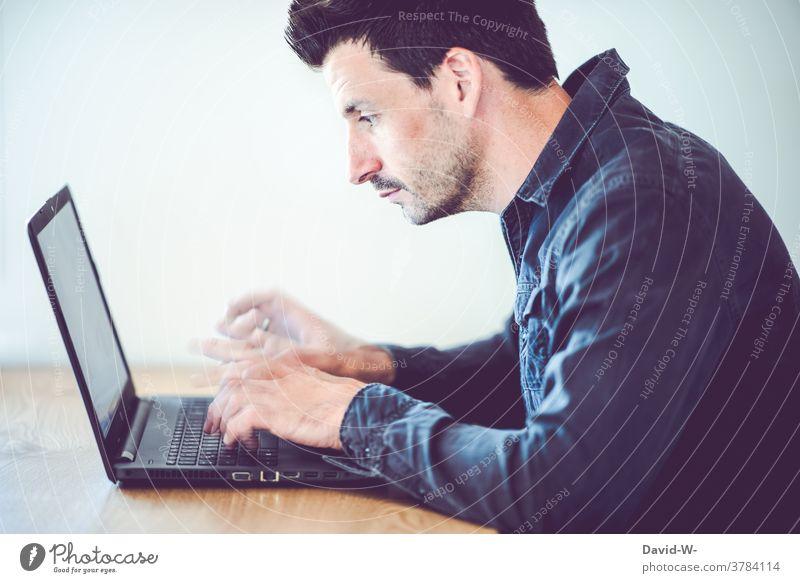 Mann tippt mit schnellen Fingern auf seinem Laptop herum tippen Geschwindigkeit konzentriert arbeiten Schreibtisch Homeoffice hektisch zeitdruck Erfolg
