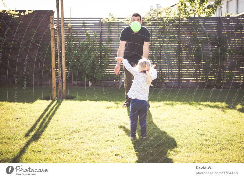 Vater und Kind spielen zusammen mit dem Ball Garten Zusammensein Frühling Sommer Zeit Familienzeit gemeinsam Tochter