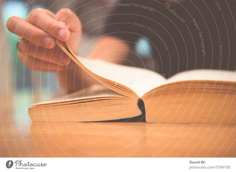 Frau liest ein Buch und blättert die Seite um lesen umblättern nachschlagen Wissen Hand lernen Roman Lesestoff Buchseite Tisch sitzen