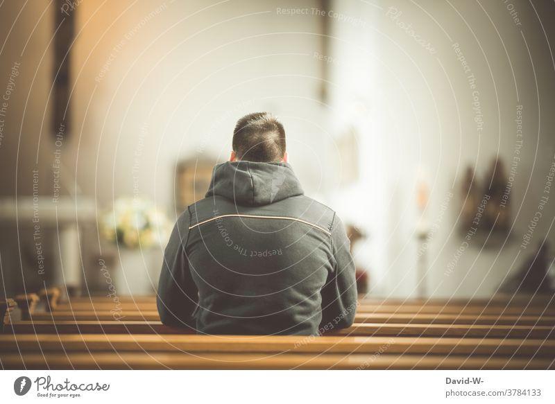 Mann sitzt in der Kirche in einer Kirchenbank und betet beten Glaube Religion Hoffnung Gebet betend glauben anonym