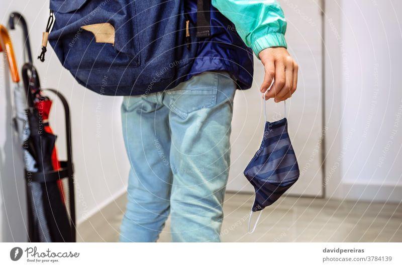 Unbekannter Junge mit Rucksack, der eine Maske in der Hand hält unkenntlich Beteiligung Mundschutz Coronavirus zur Schule gehen covid-19 Virus Kind