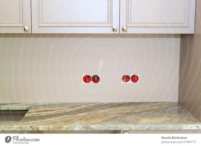 Marmor-Arbeitsplatte mit Ausschnitt für Spüle oder Herd in einer modernen, klassischen Küche. Wandsteckdosen mit freiliegenden elektrischen Leitungen, die vor der Installation der Marmorverkleidung der Küchenwand entfernt wurden
