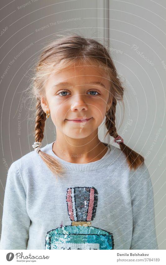 Nahaufnahme eines schönen сaucasian kleinen Mädchens mit Zöpfen in einem gemütlichen Pullover, das mit einem charmanten Lächeln in die Kamera blickt und sich vor der hellen Fläche der Betonmauer postiert. Konzept der glücklichen Kindheit