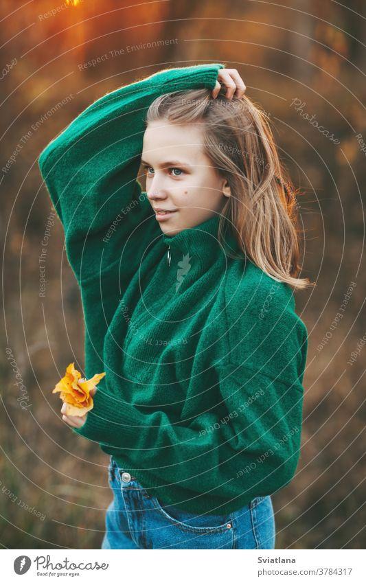 Porträt eines schönen Teenagermädchens mit blonden Haaren und blauen Augen mit einem Lächeln im Gesicht und einem herbstlich gelben Blatt im Park. Herbst Glück