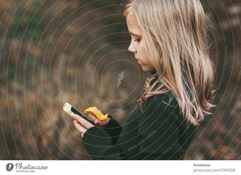 Blondes Teenagermädchen steht mit dem Telefon und schreibt im Park unter freiem Himmel eine Nachricht. jung klug Kind Langeweile blond verwenden schön Mädchen