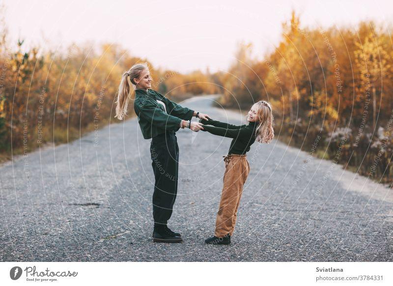 Glückliche reife Mutter und ihre blonde kleine Tochter, die sich beim Spaziergang im Herbst im Park im Freien umarmen und lachen Frau Mama Lächeln lieblich