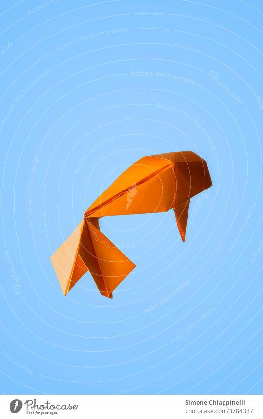 Origami orange-goldener Fisch auf hellblauem Hintergrund Origami-Papier Goldener Fisch Koi Koi-Karpfen hell-blau hellblauer Hintergrund Tier Farbfoto