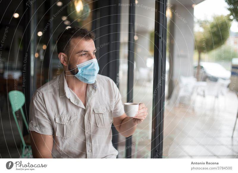 Mann mit chirurgischer Maske trinkt Kaffee und schaut aus dem Fenster Mundschutz Gesicht covid-19 Coronavirus Verschmutzung Allergie Person Menschen eine Person