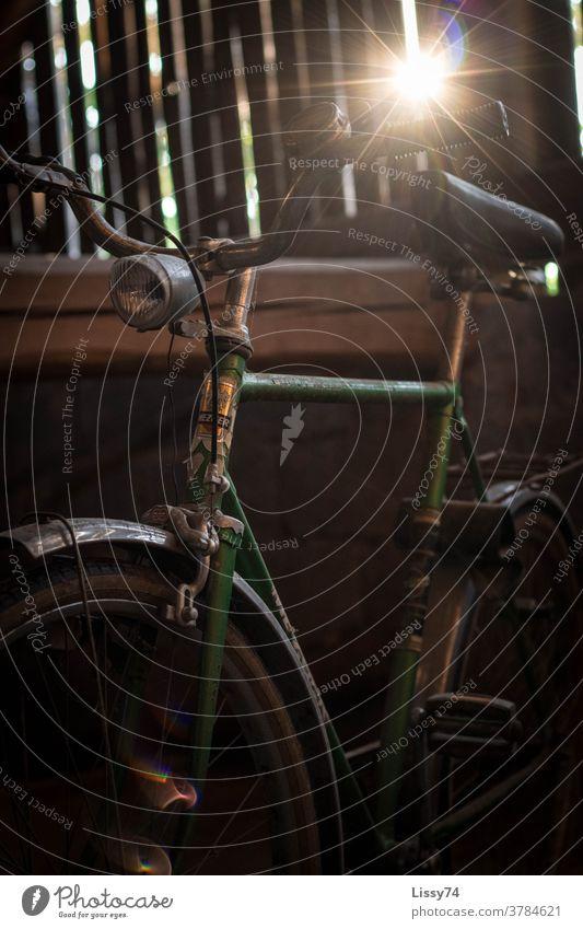 Altes, grünes Herren-Fahrrad auf dem Scheunenboden, angestrahlt durch die von außen, zwischen den Holzbrettern eindringenden Sonnenstrahlen Herrenfahrrad Retro