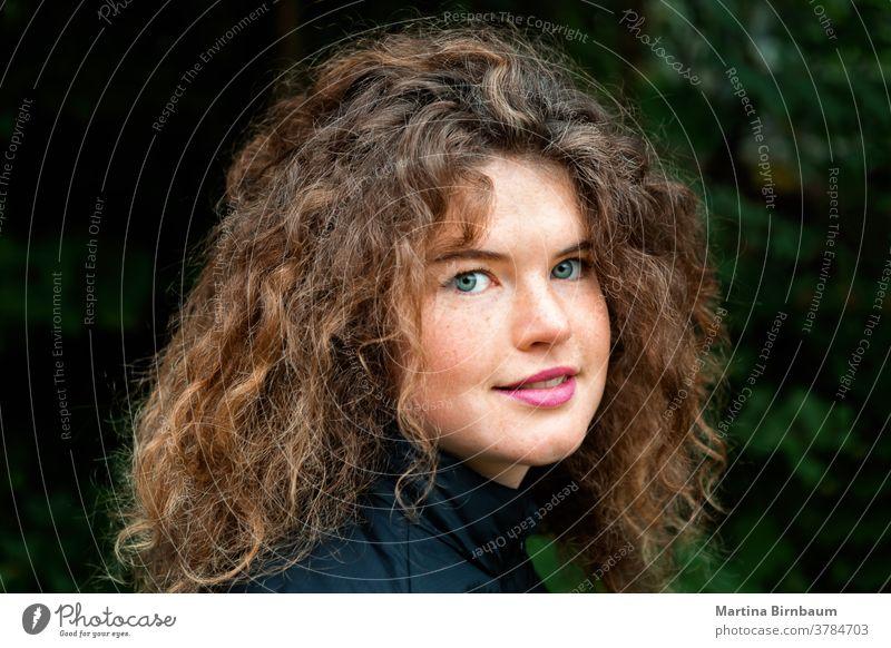 Junge natürliche Frau mit Sommersprossen und wild lockigem Haar schaut in die Kamera jung Gesicht krause Haare Mädchen eine schön Kaukasier Schönheit Person