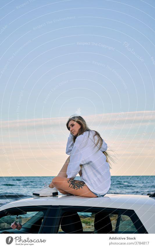 Entspannte Frau auf dem Dach eines Autos am Meer PKW Reisender sich[Akk] entspannen Seeküste Urlaub Fernweh Abenteuer Sonnenuntergang Abend MEER Sommer Natur