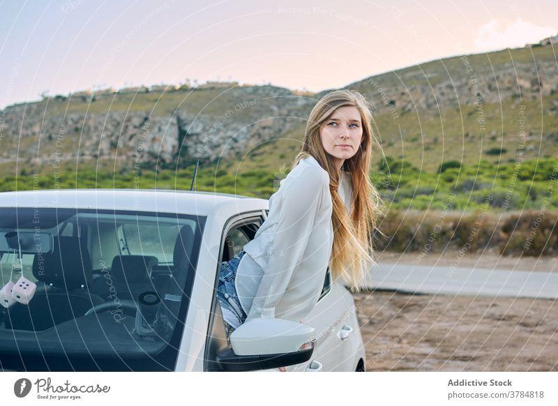 Begeisterte weibliche Reisende aus dem Autofenster PKW Fenster Frau genießen sorgenfrei reisen Reisender Fernweh Automobil Sommer Natur Urlaub Abend ruhen